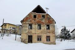 Maison ruinée abandonnée avec les fenêtres cassées et la façade tombée couvertes dans la neige Photographie stock libre de droits