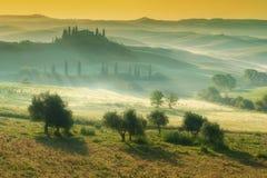 Maison toscane sur la colline brumeuse en d'Orcia de Val, Italie Photographie stock