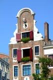 Maison type à Amsterdam avec des géraniums dans l'hublot Photo libre de droits