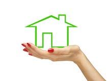 Maison verte chez la main de la femme d'isolement sur le blanc Image libre de droits