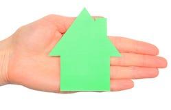Maison verte dans des mains d'isolement sur le blanc Images stock