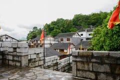 Maisons démodées de Hillside près du mur en pierre en ressort nuageux photos stock