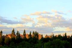 Maisons de ceinture de forêt au coucher du soleil Photo stock