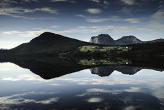 Maisons de ferme se reflétant dans un lac Photographie stock
