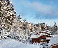 Maisons de logarithme naturel dans le paysage neigeux de l'hiver Photographie stock