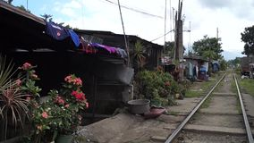 Maisons de logement sur les côtés des voies ferrées vues d'un chariot mobile de chariot banque de vidéos