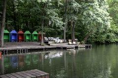 Maisons de plage rouges, bleues et vertes près d'un lac Images libres de droits