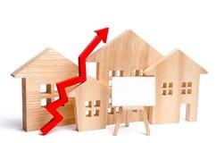 Maisons en bois avec une flèche vers le haut de et un espace rouges pour le texte concept de forte demande pour les immobiliers C photos stock