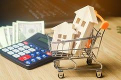 Maisons en bois dans un chariot à supermarché, l'argent et une calculatrice Analytics de marché de l'immobilier Concept 6 d'immeu image stock