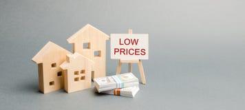 Maisons en bois et une affiche avec les petits prix de mots Le concept de r?duire la valeur des immobiliers Int?r?ts hypoth?caire images libres de droits