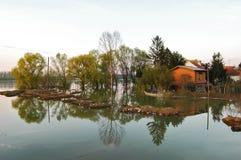 Maisons en crue et terre en rivière Photographie stock libre de droits