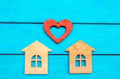 Maisons et coeur en bois sur un fond bleu Amour de concept Photographie stock libre de droits