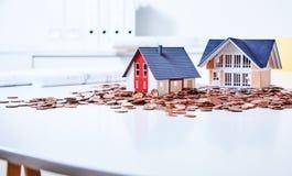 Maisons miniatures se tenant parmi des pièces de monnaie Photographie stock libre de droits
