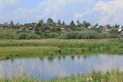 Maisons russes de village au-dessus d'une rivière image stock