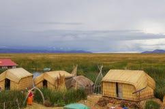 Maisons traditionnelles des personnes locales dans des îles d'Uros sur le Lac Titicaca photo stock