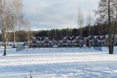 Maisons urbaines mignonnes près de la rivière pendant le jour d'hiver ensoleillé photo stock