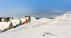 Maisons vertes, bleues, rouges et vertes d'inuit couvertes dans la neige au f Images libres de droits
