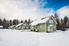 Maisons vertes dans la forêt de neige Images libres de droits