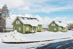 Maisons vertes dans la forêt de neige Photos stock