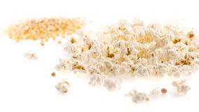 Maissaatgut und Popcorn auf dem weißen Hintergrund Lizenzfreie Stockbilder