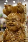 Maitreya buddha and little monk. Woodcarving Stock Image
