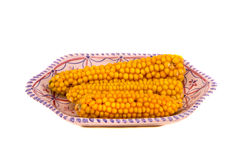 Maize cobs in decorative plate isolated on white Stock Photos