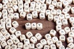 Maj bokstav tärnar ord Arkivbild