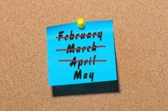 Maj månadbörjan Text som är skriftlig på den blåa klistermärken som klämmas fast på noticeboarden med korsat ut mars och April mo Arkivfoton