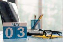 Maj 3rd Dag 3 av månaden, kalender på bakgrund för affärskontor, arbetsplats med bärbara datorn och exponeringsglas Vårtid som är Royaltyfri Fotografi
