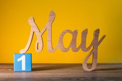 Maj 1st dag 1 av kan månaden, kalender på gul bakgrund med träsned bokstäver Fjädra den tid… ron lämnar, naturlig bakgrund Fotografering för Bildbyråer