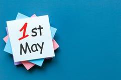 Maj 1st dag 1 av kan månaden, kalendern på högen av anmärkningar på blå bakgrund med kopieringsutrymme för mall eller modellen Vå Fotografering för Bildbyråer