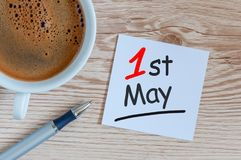 Maj 1st dag 1 av kan månaden, kalendern på kontor eller hemtabellen med morgoncoffekoppen Vårtid, internationell arbets- dag Royaltyfri Bild