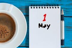 Maj 1st dag 1 av månaden, kalender på den vita notepaden med morgonkaffekoppen på bakgrund för arbetsställe Vårtid, överkant Royaltyfri Fotografi