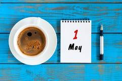 Maj 1st dag 1 av månaden, kalender på den vita notepaden med morgonkaffekoppen på bakgrund för arbetsställe Top beskådar Arkivfoton