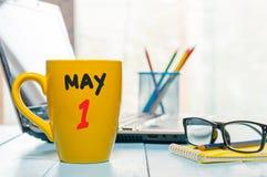 Maj 1st dag 1 av månaden, kalender på morgonkaffekoppen, bakgrund för affärskontor, arbetsplats med bärbara datorn och exponering Royaltyfri Bild