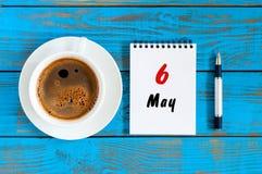 Maj 6th Dag 6 av kan månaden, att calendar skriftligt på morgonkaffekoppen på den blåa trätabellen, bästa sikt Fjädra den tid… ro Arkivbild