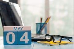 Maj 4th Dag 4 av månaden, kalender på bakgrund för affärskontor, arbetsplats med bärbara datorn och exponeringsglas Vårtid som är Royaltyfria Bilder