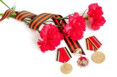 9 Maj Victory Day festlig bakgrund - jubileummedaljer av det stora patriotiska kriget med röda nejlikor och det St George bandet Arkivbild