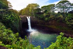 Majesitc Rainbow Falls waterfall in Hilo, Wailuku River State Park, Hawaii. The falls flows over a natural lava cave, the mythological home to Hina, an ancient Royalty Free Stock Image