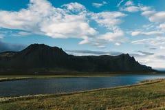 majestätische isländische Landschaft mit ruhigem Fluss zwischen felsigen Bergen und grasartig lizenzfreies stockbild