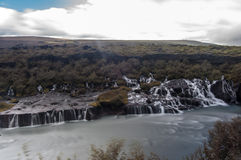 Majestätische Wasserfälle mit Felsen und Gras herum Lizenzfreie Stockfotos