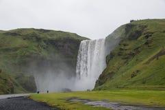 Majestätische Wasserfälle mit Felsen und Gras herum Stockbild
