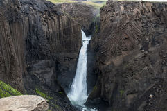 Majestätische Wasserfälle mit Felsen und Gras herum Lizenzfreie Stockfotografie