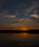 Majestätischer roter Sonnenuntergang und seine Reflexion im Fluss Lizenzfreie Stockfotografie