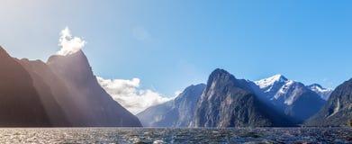 Majestätischer Schnee bedeckte Spitzen von Milford Sound mit Sonnenstrahlen mit einer Kappe Fjord Stockfotos