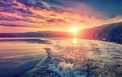 Majestätisk solnedgång på sjön färgrika moln i himlen som gloving i solljus, reflrcted i vattnet Royaltyfria Bilder