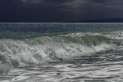 Majestätisk turkos och grön dyning med solljusreflexioner som kraschar in i en strand på en sommardag för blå himmel i Sicilien arkivbild