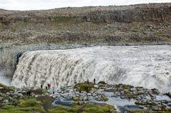 Majestätiska vattenfall med vaggar och gräs omkring Arkivbilder