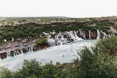 majestätiskt landskap med Hraunfossar vattenfall och grön vegetation på kullar arkivbild