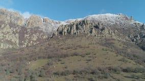 Majestatyczna rockowa formacja na zielonej zbocze góry zakrywającej krzakami na jasnym słonecznym dniu przeciw błękitnemu jasnemu zdjęcie wideo